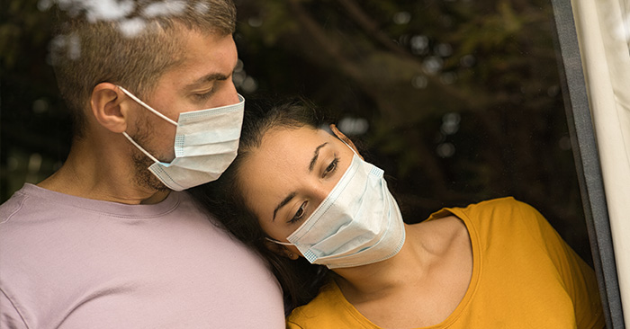 couple with face masks looking out window