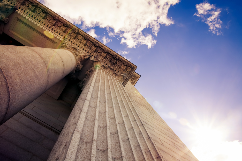 looking up at the pillars of a courthouse