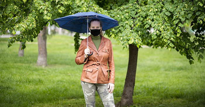 woman with facemask holding an umbrella in a park